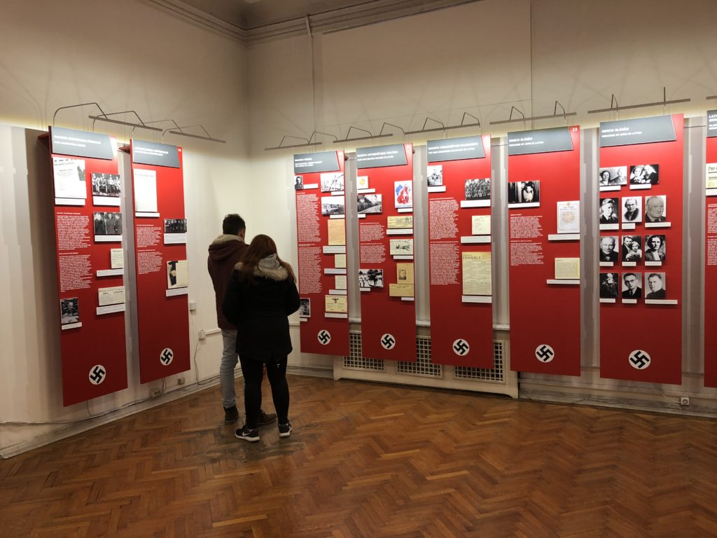 Visitors to the temporary location of the Museum of the Occupation of Latvia view part of an exhibit that tells about Nazi Germany's rule of the country. (Photo by Andris Straumanis)