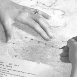 In 1957, a cartographer working in California for the U.S. Geological Survey applies adhesive-backed lettering to a topographic map of Miller Peak, Arizona. (U.S. Geological Survey)